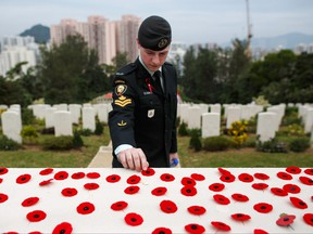 A Canadian armed forces member places a poppy over the Altar of Remembrance following the Canadian Commemorative Ceremony honouring those who died during the Battle of Hong Kong and the Second World War in Hong Kong's Sai Wan War Cemetery on Dec. 4, 2016.