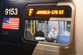 A woman with a face mask rides on the subway in Brooklyn.