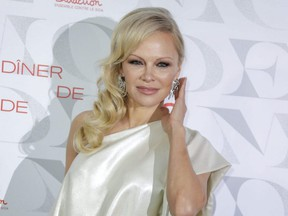 """Pamela Anderson poses during a photocall at the """"Diner de la Mode"""" (Fashion Dinner) fundraiser to benefit French anti-AIDS association Sidaction, at the Pavillon d'Armenonville in Paris, Jan. 24, 2019."""