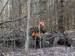 Search and rescue volunteers look through the remains of an old vehicle as the ground search for missing three year old Jude Walter Leyton who went missing Sunday near Verona, Ont. on Tuesday, March 30, 2021.