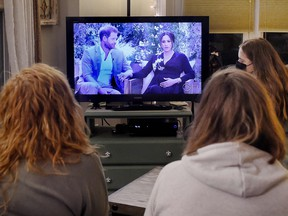 People watch a televised conversation between Prince Harry with his wife Meghan Markle and Oprah Winfrey, in Arlington, Virginia March 7, 2021.