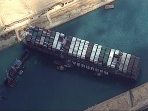 This satellite imagery released by Maxar Technologies shows tug boats and dredgers attempting to free the MV Ever Given on March 26, 2021, in the Suez Canal.