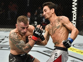 In this handout image provided by UFC, Max Holloway, right, punches Alexander Volkanovski of Australia in their UFC featherweight championship fight during the UFC 251 event at Flash Forum on UFC Fight Island on July 12, 2020 on Yas Island, Abu Dhabi, United Arab Emirates.
