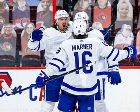 Maple Leafs' Justin Holl (left) celebrates his overtime winner against the Senators with teammates Mitch Marner and Auston Matthews on Thursday, March 25, 2021 at the Canadian Tire Centre in Ottawa.