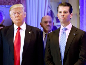 Donald Trump and his son Donald, Jr., arrive for a press conference at Trump Tower in New York, as Allen Weisselberg (middle), chief financial officer of The Trump, looks on.