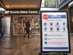 In this file photo, people arrive at the entrance to the Toronto Eaton Centre in downtown Toronto, Ontario on November 23, 2020, the first day of a new lockdown in the city.