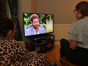 A family gather around the television in Liverpool, north west England to watch Prince Harry and his wife Meghan's explosive tell-all interview on CBS with Oprah Winfrey, on March 8, 2021, as national television in Britain shows the interview a day later then in the US.