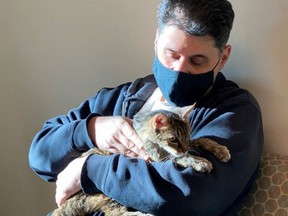 Brandy, a brown tabby cat, on Monday, Feb. 22, 2021, with her owner, Charles at the Palmdale, Calif., animal care centre.