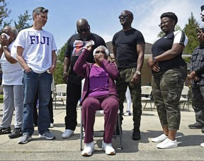 Jessie Hamilton, seated, reacts as several Louisiana State University members of Phi Gamma Delta, commonly called Fiji, surprise her with $51,765 to pay off her mortgage. Hamilton, 74, worked as a cook at the Fiji fraternity house for 14 years.