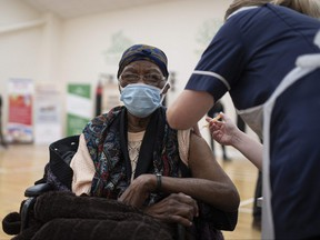 A health worker administers a dose of the AstraZeneca/Oxford COVID-19 vaccine to a patient at a vaccination centre set up at the Karimia Institute Islamic centre and Mosque in Nottingham, central England on April 6, 2021.