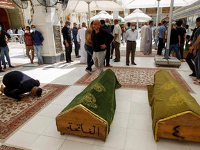 A man prays next to the coffins of people who were killed in a fire at a hospital in southeastern Baghdad that had been equipped to house COVID-19 patients, in Najaf, Iraq, Sunday, April 25, 2021.