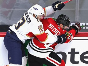 Vinnie Hinostroza (13) of the Florida Panthers collides with Ian Mitchell of the Chicago Blackhawks at the United Center on March 25, 2021 in Chicago.