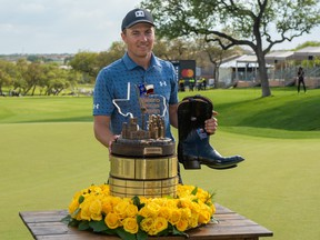Jordan Spieth holds the trophy and champion's boots after winning the Valero Texas Open golf tournament in San Antonio, Texas, April 4, 2021.