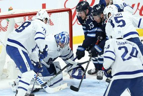 Winnipeg Jets forwards Pierre-Luc Dubois (centre) and Paul Stastny (centre right) try to jam a puck past Toronto Maple Leafs goaltender Jack Campbell during last night's game in Winnipeg.KEVIN KING/Postmedia Network