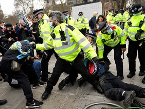 Police officers restrain demonstrators during a protest in London, Britain, April 3, 2021.