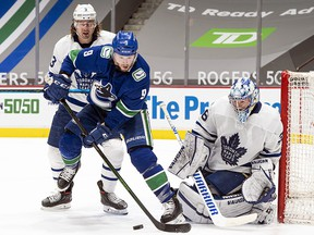 J.T. Miller of the Vancouver Canucks tries to redirect the puck on goalie Jack Campbell of the Toronto Maple Leafs while being checked by Justin Holl at Rogers Arena on April 17, 2021 in Vancouver.