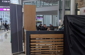 Unmasked diners enjoy a meal at a restaurant inside Terminal 1 of Toronto Pearson Airport in April. Airports are specifically exempted from provincial prohibitions on indoor dining.