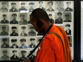 A Buddhist monk looks at pictures of victims of the Khmer Rouge regime at Tuol Sleng Genocide Museum in Phnom Penh, Cambodia June 1, 2016.