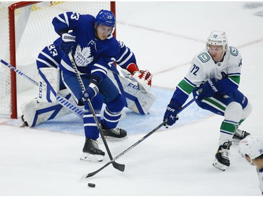 Toronto Maple Leafs Travis Dermott D (23) keeps the puck away from Vancouver Canucks Travis Boyd C (72) during the second period in Toronto on Thursday April 29, 2021. Jack Boland/Toronto Sun/Postmedia Network