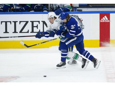 Toronto Maple Leafs Timothy Liljegren D (37) collides with Vancouver Canucks Jake Virtanen LW (18) during the first period in Toronto on Thursday April 29, 2021. Jack Boland/Toronto Sun/Postmedia Network