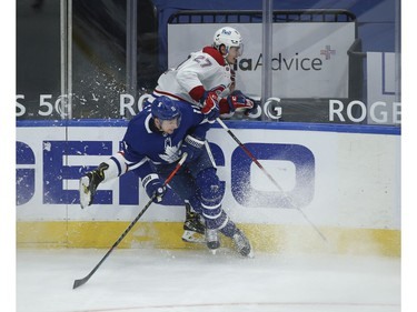 Toronto Maple Leafs Zach Hyman C (11) and Montreal Canadiens Alexander Romanov D (27) collide along the boards during the first period in Toronto on Wednesday April 7, 2021. Jack Boland/Toronto Sun/Postmedia Network