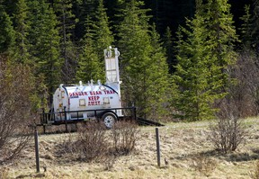 A bear trap and signs set up just southwest of Water Valley where a woman was attacked and killed by a grizzly bear on Wednesday, May 26, 2021.