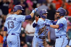 Marcus Semien #10 of the Toronto Blue Jays celebrates with Lourdes Gurriel Jr. #13 and Cavan Biggio #8 after hitting a three-run home run during the ninth inning against the Houston Astros at Minute Maid Park on May 8, 2021 in Houston, Texas.
