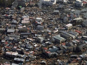 This file photo taken on March 12, 2011 shows collapsed houses and debris in a field in Kesennuma, Miyagi prefecture on March 12, 2011 after the massive 8.9-magnitude earthquake and tsunami hit Japan.