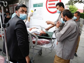 People transport an injured woman to a hospital after a blast in Kabul, Afghanistan May 8, 2021.