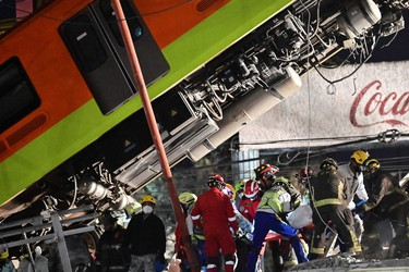 Rescue workers remove a body from a train carriage after an elevated metro line collapsed in Mexico City on May 4, 2021. (Photo by PEDRO PARDO/AFP via Getty Images)