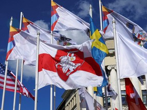 A historical white-red-white flag of Belarus flies next to national flags of nations participating in the IIHF World Ice Hockey Championships in Riga, Latvia, Monday, May 24, 2021.