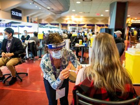 A health-care worker administers the Pfizer/BioNTech COVID-19 vaccine at Woodbine Racetrack pop-up vaccine clinic in Toronto, May 5, 2021.
