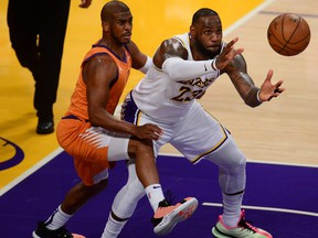 Los Angeles Lakers forward LeBron James, right, gets the ball against the defence of Phoenix Suns guard Chris Paul during the second half in Game 4 of the first round of the 2021 NBA Playoffs at Staples Center in Los Angeles, Calif., May 30, 2021.