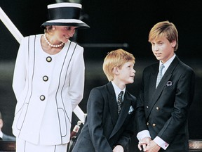 In this file photo taken on August 19, 1995 Princess Diana and their children William and Harry watch the march past on a dais on the mall as part of the commemorations of VJ Day.