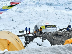 In this picture taken on May 1, 2021 expedition members clear an area to set up tents at Everest base camp in the Mount Everest region of Solukhumbu district.