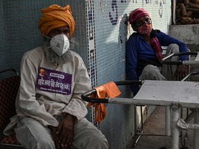 In this photograph taken on May 12, 2021 volunteers rest as they work at a crematorium in New Delhi amid the Covid-19 coronavirus pandemic.