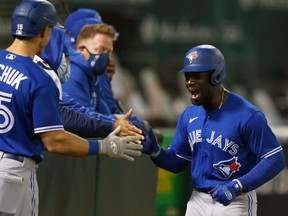 Pinch runner Jonathan Davis celebrates with his teammates after scoring a run  as the Blue Jays beat the Athletics on Wednesday night. GETTY IMAGES
