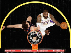 LeBron James of the Los Angeles Lakers attempts a lay-up past Dario Saric of the Phoenix Suns at Phoenix Suns Arena on May 23, 2021 in Phoenix.