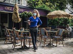 A waitress poses in front of the terrace of her cafe in Paris on May 19 2021, as restaurant and bar terraces re-open as part of an easing of the nationwide lockdown due to the Covid-19 pandemic.