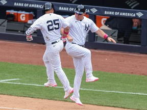 New York Yankees shortstop Gleyber Torres, left, celebrates with third base coach Phil Nevin after hitting a home run during the sixth inning against the Washington Nationals at Yankee Stadium in New York, May 9, 2021.