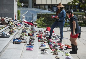 215 pairs of kids shoes line the steps of the Vancouver Art Gallery Friday, May 28, 2021 in response to the revelation that 215 children's remains were discovered this week at the site of the former Kamloops residential school.