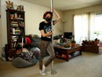 April Haze, a San Jose-based stripper, poses for a photo with her pole at her home April 15, 2021.