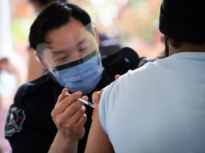 Surrey firefighter Justin Sayson administers a first dose of the Pfizer COVID-19 vaccine to a man at a walk-up vaccination clinic at Bear Creek Park, in Surrey, B.C., on Monday, May 17, 2021.