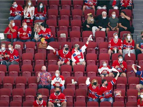 Socially distanced Montreal Canadiens fans cheer during a playoff game against the Winnipeg Jets in Montreal Monday June 7, 2021.