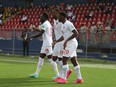 Canada's Alphonso Davies, 19, Cyle Larin, 17 and Jonathan David, 20, celebrate a goal against Haiti in World Cup qualifying in Port-au-Prince, Haiti on June 12, 2021. Canada won 1-0.