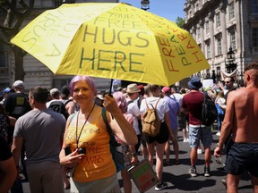 An anti-lockdown and anti-vaccine demonstrator holds up an umbrella as she takes part in a protest in Downing Street, amid the COVID-19 pandemic, London, June 14, 2021.