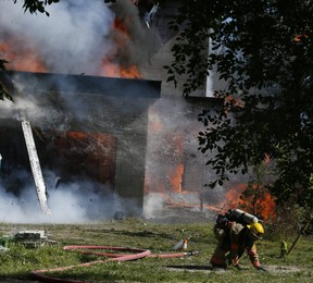 A firefighter drops the hose and leaps to safety as flaming timbers fall while battling a house fire on Beachview St. In Ajax on Tuesday, June 15, 2021.