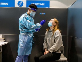 Jennifer Eriksson is tested as passengers arrive at Toronto's Pearson airport after mandatory coronavirus testing took effect for international arrivals in Mississauga February 1, 2021.