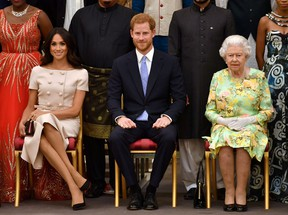 Queen Elizabeth, Prince Harry and Meghan, the Duchess of Sussex pose for a picture with some of Queen's Young Leaders at a Buckingham Palace reception following the final Queen's Young Leaders Awards Ceremony, in London on June 26, 2018.