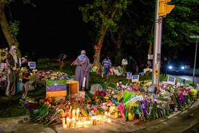 People gather at a makeshift memorial at the fatal crime scene where a man driving a pickup truck jumped the curb and ran over a Muslim family in what police say was a deliberately targeted anti-Islamic hate crime, in London, Ont., June 8, 2021.